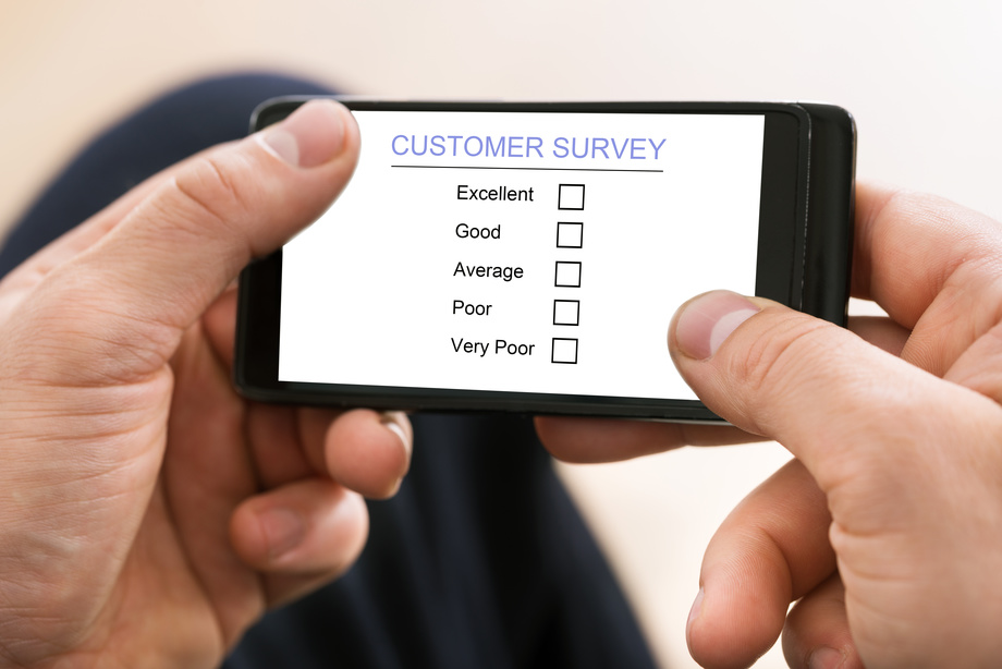 Close-up Of Man Holding Mobile Phone Showing Customer Survey Form