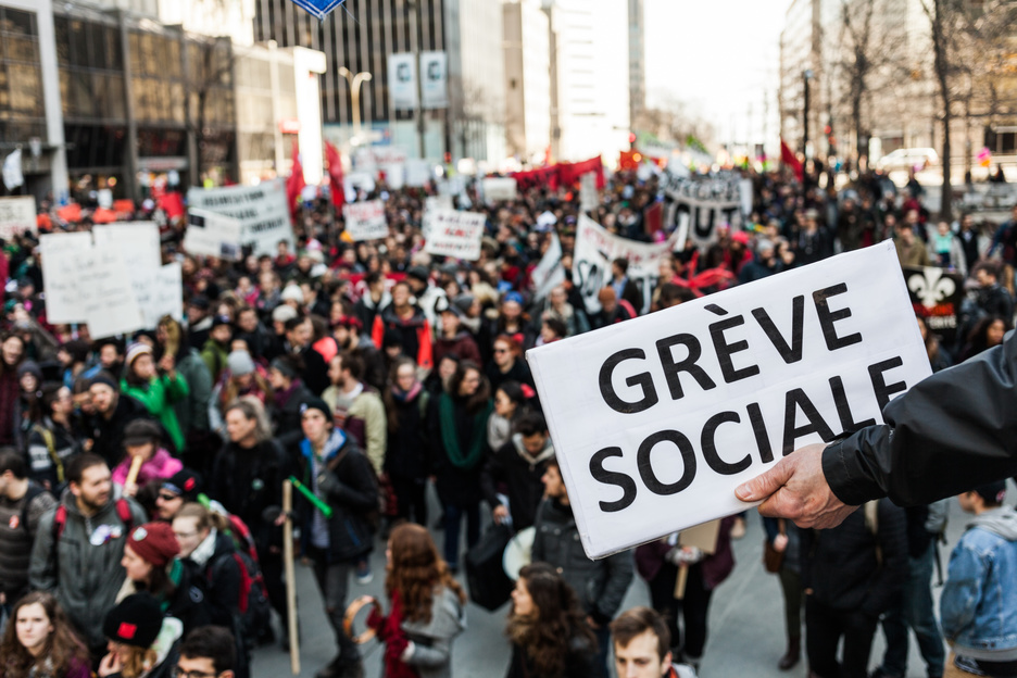 """MONTREAL, CANADA, APRIL 02 2015. Riot in the Montreal Streets to counter the Economic Austerity Measures. Someone Holding a Sigh Saying """"Greve Sociale"""" (French) with Blurry Protester in Background."""